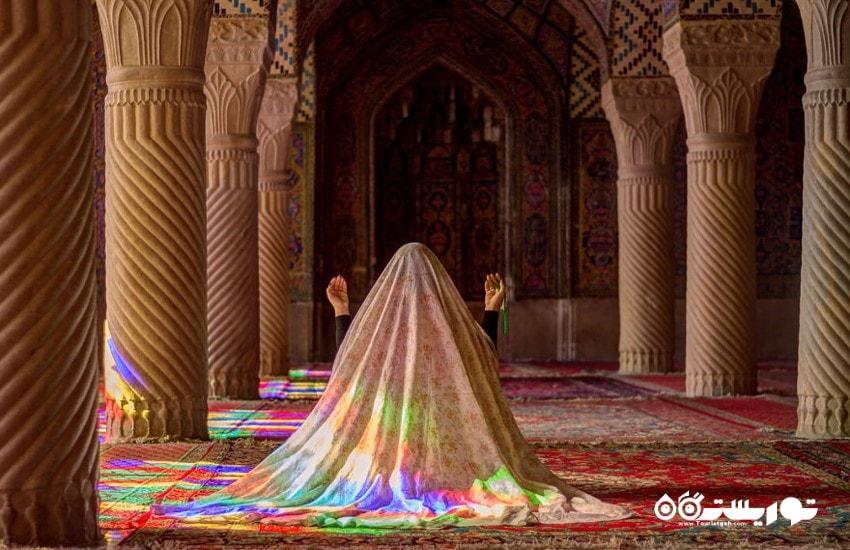 زن جوانی که در شبستان اصلی مسجد مشغول راز و نیاز است